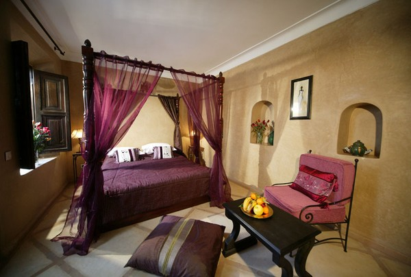 Giường canopy ấn tượng với chất liệu gỗ và mành treo màu tím.